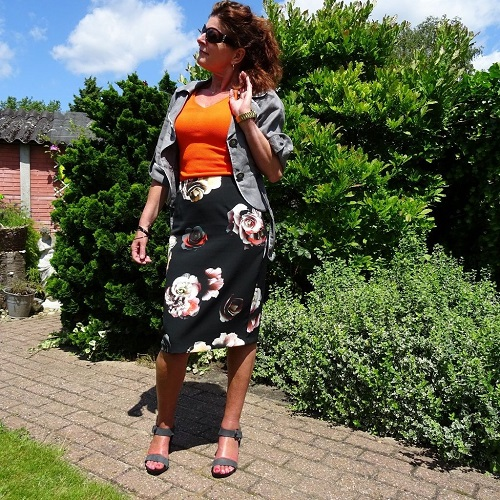 Floral skirt and orange top with grey jacket