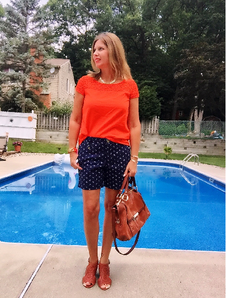 orange tee in front of a swimming pool