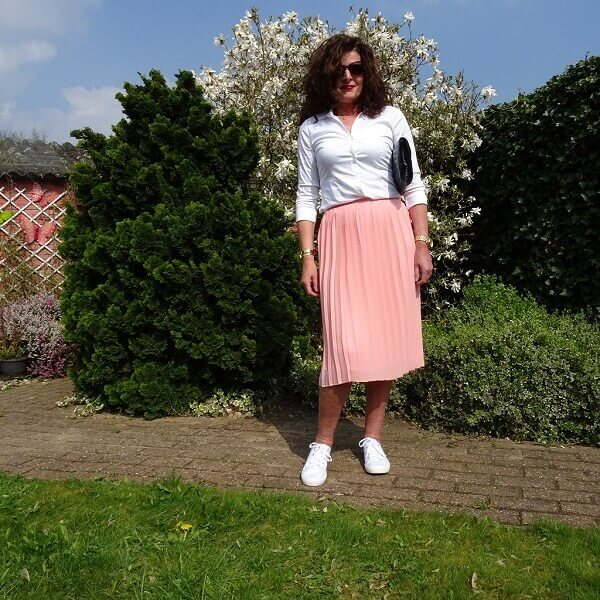 pink pleated skirt and white sneakers
