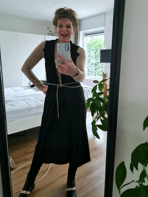 wearing a black vest over a silk skirt . Belted with a chain belt