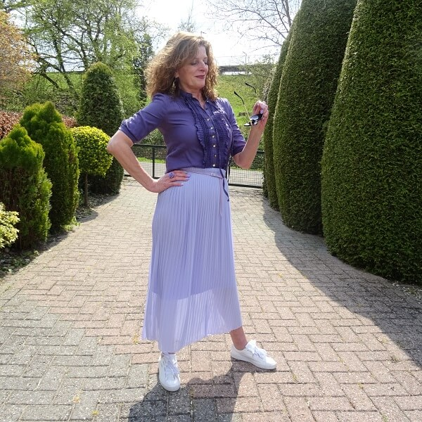 white sneakers under a pleated skirt