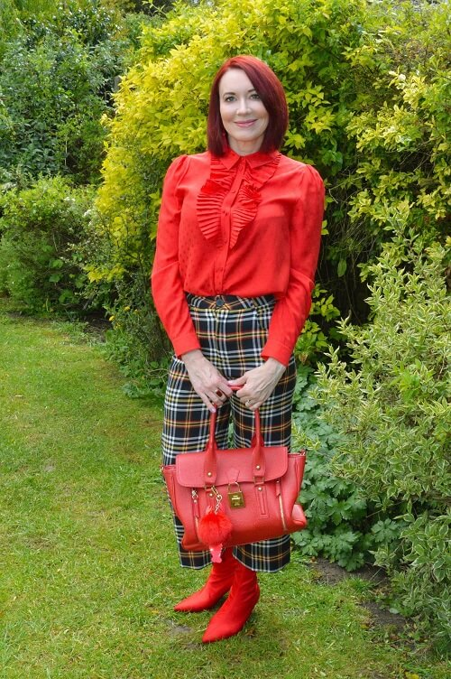red blouse on tartan trousers