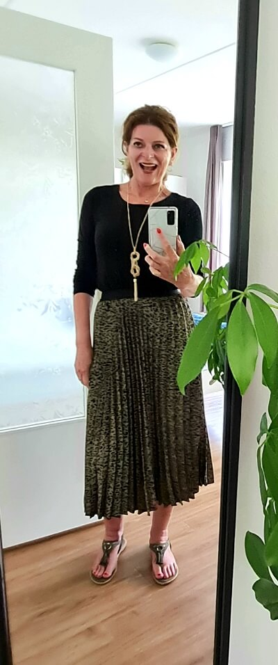 black simple top on a leopard pleated skirt