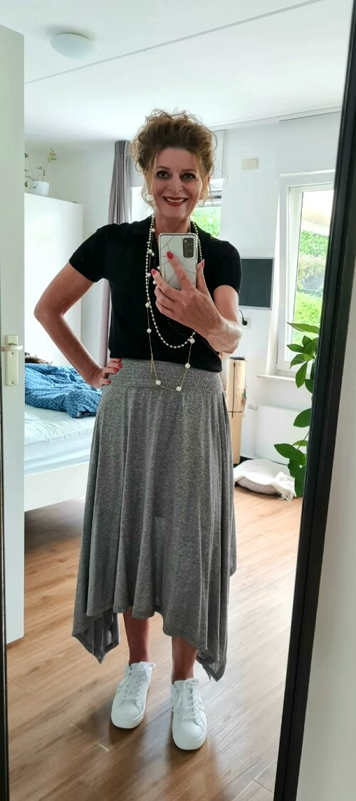 grey skirt white sneakers black top and pearls