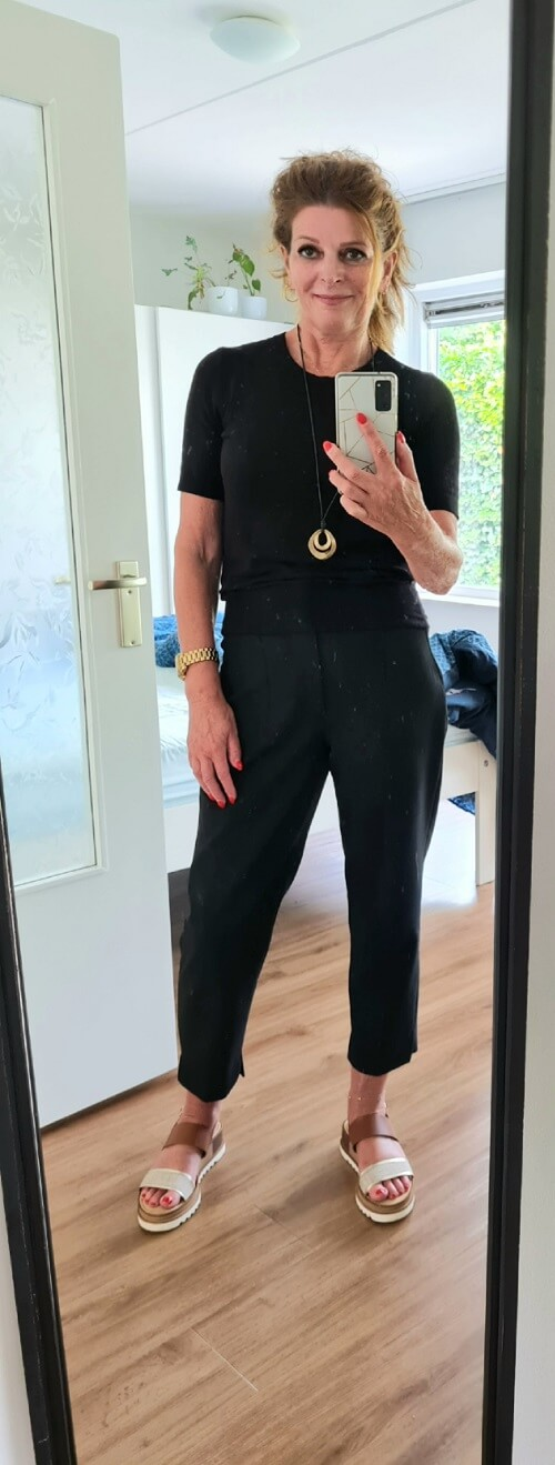 black trousers and top and tan sandals